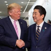U.S. President Donald Trump is greeted by Prime Minister Shinzo Abe at the Group of 20 summit in Osaka on June 28, 2019. | BLOOMBERG