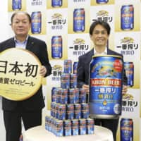 Kirin Brewery President Takayuki Fuse (left) holds a sign reading 'Japan's first' in promoting its new zero-carb beer in Tokyo on Thursday. | KYODO