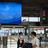 An airline employee talks with a passenger at Narita International Airport in Chiba Prefecture on Aug. 19. | AFP-JIJI