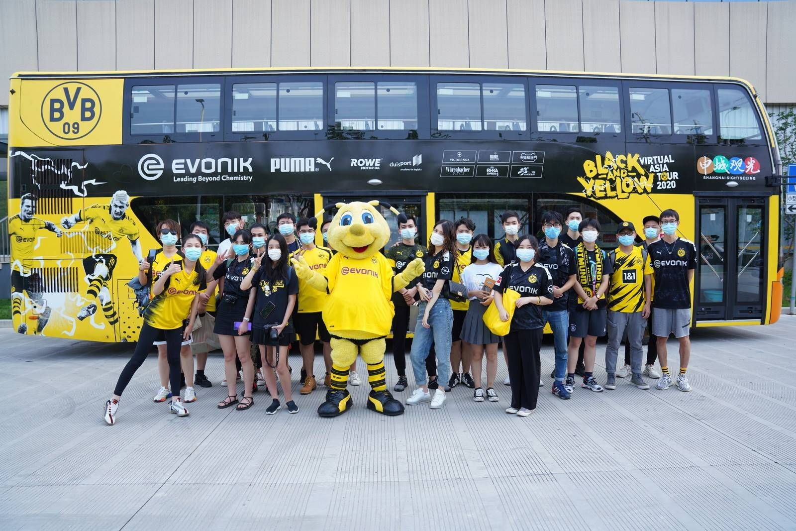 Dortmund mascot Emma poses with Chinese fans in front of a bus promoting the team's virtual tour of Asia on Aug. 19 in Shanghai. | BORUSSIA DORTMUND
