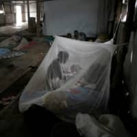 A South Sudanese refugee takes care of her baby under a mosquito net in a transit tent at a refugee camp in Uganda in 2017. Malaria affects more than 200 million people worldwide and killed an estimated 405,000 people in 2018 — most of them babies and children under five years old. | REUTERS