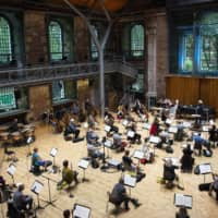 Members of the London Symphony Orchestra practice social distancing Thursday as they rehearse for an upcoming performance. | AP