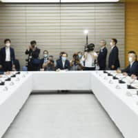 Ministers discuss the government's coronavirus response at the Prime Minister's Office on Friday. | KYODO