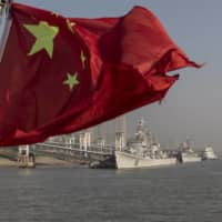 A Chinese national flag flies from a ferry as retired People's Liberation Army Navy frigates  sit anchored on the Yangtze River in Wuhan, Hubei, China, in December 2019.