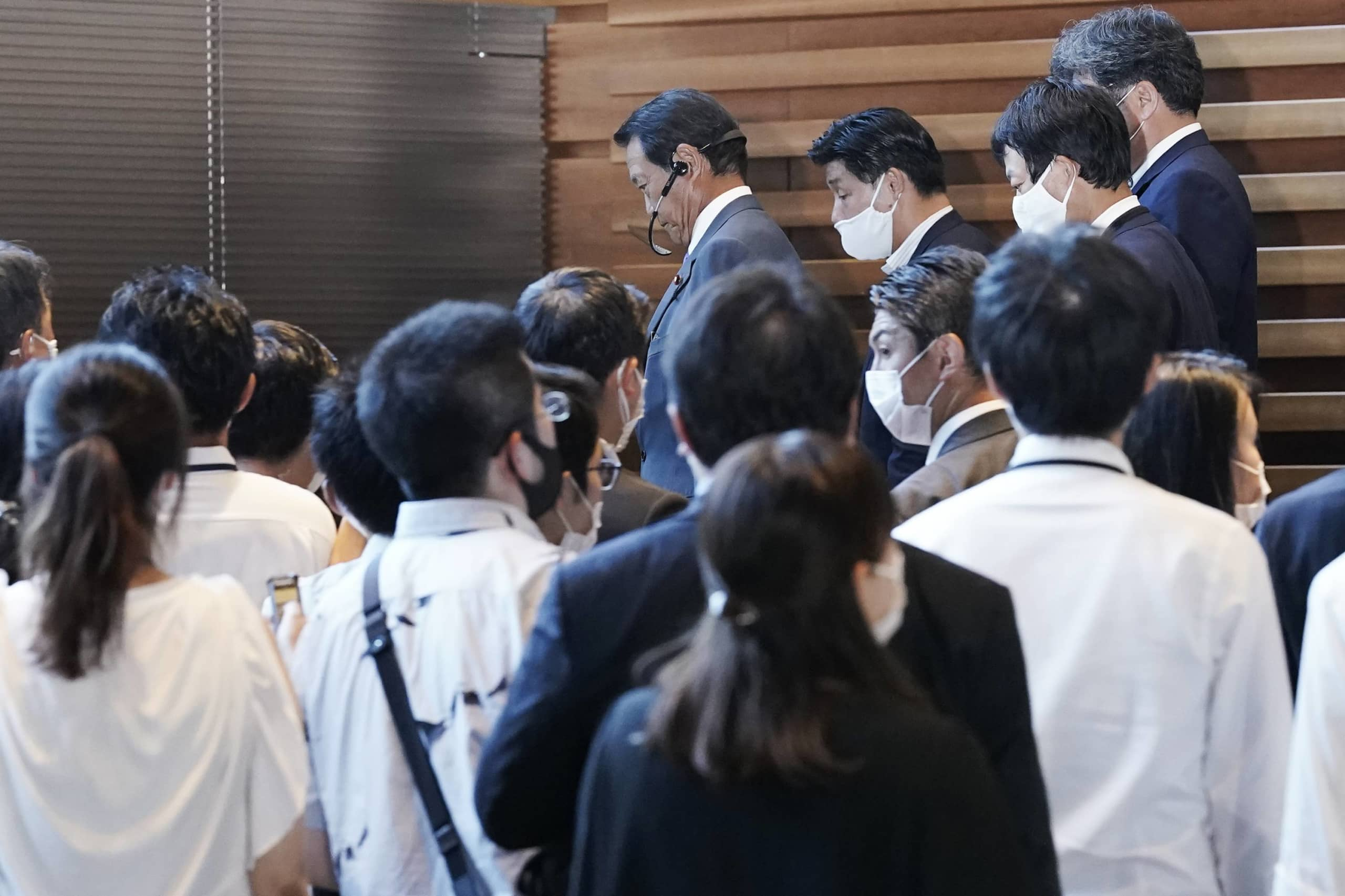 Deputy Prime Minister and Finance Minister Taro Aso (center, top) is surrounded by journalists at the Prime Minister's Office in Tokyo on Friday.   AP