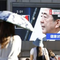 Pedestrians in Osaka's Dotonbori area watch a televised broadcast of a press conference in which Prime Minister Shinzo Abe announced his intention of stepping down on Friday. | KYODO