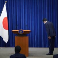 Prime Minister Shinzo Abe bows toward the national flag at the start of a press conference on Friday in which he announced his decision to step down due to a chronic health problem. | AP