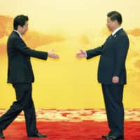 Prime Minister Shinzo Abe greets Chinese President Xi Jinping during an Asia-Pacific Economic Cooperation meeting in Beijing in November 2014. | AP