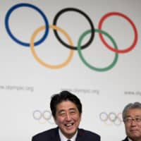 Prime Minister Shinzo Abe celebrates in September 2013 after officially signing the contract to host the 2020 Tokyo Olympic Games. | AP