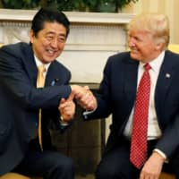 Prime Minister Shinzo Abe shakes hands with U.S. President Donald Trump during their meeting in the Oval Office at the White House in Washington in February 2017. | REUTERS