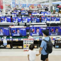 A news conference by Prime Minister Shinzo Abe is seen on TVs at an electronics store in Urayasu, Chiba Prefecture, on Friday. | KYODO