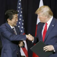 Prime Minister Shinzo Abe and U.S. President Donald Trump shake hands in New York on Sept. 25, 2019, after reaching a bilateral trade agreement.  | KYODO