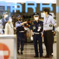 Police investigate the crime scene at a shopping mall in Fukuoka on Friday night. | KYODO
