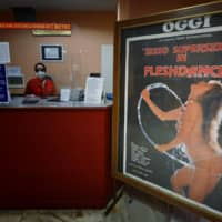 An employee wearing a face mask waits at the ticket counter as a porn film poster stands in the entrance hall of the Ambasciatori, Rome's last porn cinema theater, on Wednesday. | AFP-JIJI