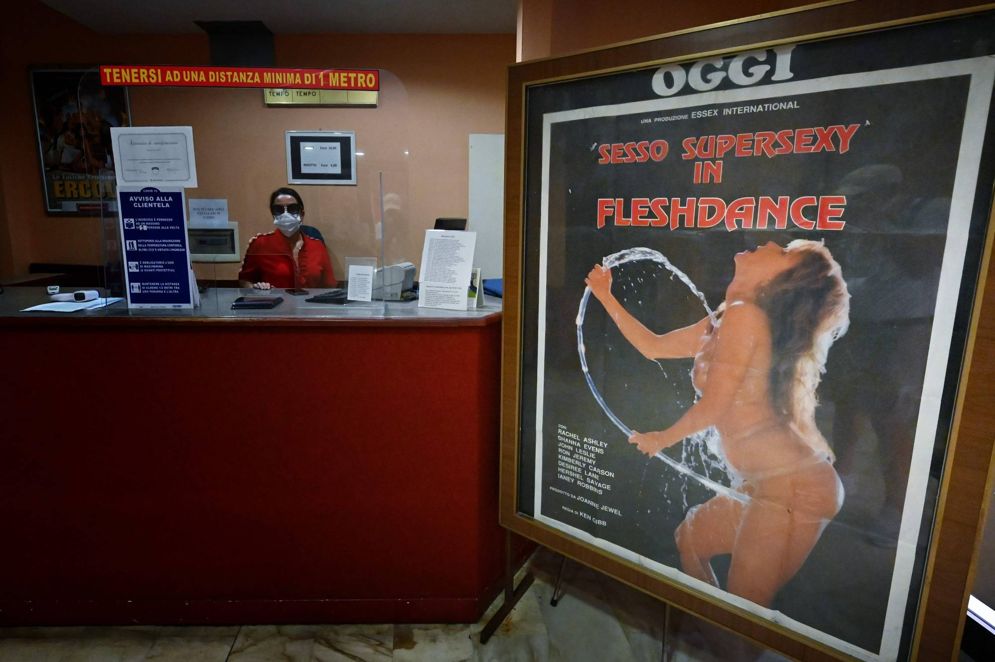 An employee wearing a face mask waits at the ticket counter as a porn film poster stands in the entrance hall of the Ambasciatori, Rome's last porn cinema theater, on Wednesday.   AFP-JIJI