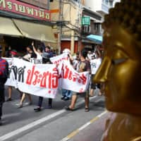 Pro-democracy protesters hold a banner during a rally in Bangkok on Friday. | REUTERS