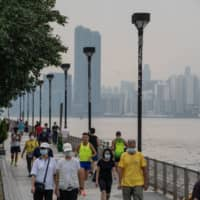 People jog along the waterfront in Hong Kong on Friday. Chinese authorities have detained a dozen activists from Hong Kong who were attempting to leave the territory via speedboat. | BLOOMBERG