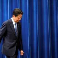 Prime Minister Shinzo Abe walks away after delivering a news conference in Tokyo on Friday. | POOL / VIA REUTERS