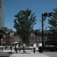 Pedestrians cross a street in the Marunouchi District of Tokyo on Friday. | BLOOMBERG