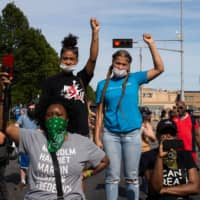 Demonstrators raise their fists as speakers talk about the shooting of Jacob Blake during a rally in Kenosha, Wisconsin, on Saturday.    AFP-JIJI