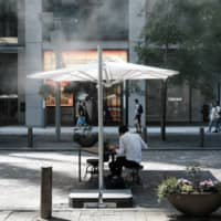 A person dines as pedestrians walk past cooling mist sprays in Tokyo's Marunouchi district on Friday. | BLOOMBERG