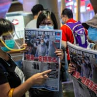 People hold up copies of the Apple Daily as they protest for press freedom inside a mall in Hong Kong on Aug. 11, a day after authorities conducted a search of the newspaper's headquarters after the company's founder Jimmy Lai was arrested under the new national security law. | AFP-JIJI