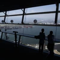 People look out of the observation deck of the Osaka Prefectural Government Sakishima Building at Yumeshima island in May 2014. Osaka, Japan's third-biggest metropolis, proposed the reclaimed island in Osaka Bay as a casino resort site.  | BLOOMBERG