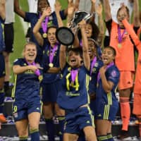 Lyon's Saki Kumagai lifts the Women's Champions League trophy after the team's win against Wolfsburg on Sunday in San Sebastian, Spain. | POOL / VIA REUTERS