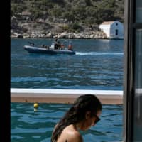 A woman sits in a cafe on the tiny Greek island of Kastellorizo on Friday as a Greek army rib returns from patrol. | AFP-JIJI
