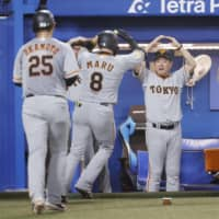 The Giants celebrate after a two-run home run by Yoshihiro Maru against the Swallows on Thursday at Jingu Stadium. | KYODO