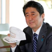 U.S. President Donald Trump and Prime Minister Shinzo Abe hold hats they signed, reading 'Donald & Shinzo Make Alliance Even Greater,' before lunch and a round of golf at Kasumigaseki Country Club in Kawagoe, Saitama Prefecture, in November 2017. | REUTERS