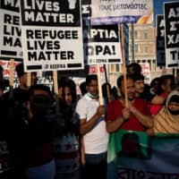 Refugees and migrants demonstrate outside the Greek parliament against a government decision that refugees staying in apartments funded by a European Union and UNHCR program should leave their accommodation, in Athens, Greece, in June.    REUTERS