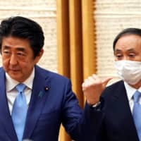 Prime Minister Shinzo Abe and Chief Cabinet Secretary Yoshihide Suga attend a May news conference in Tokyo. Suga, once thought of as a dark horse candidate to succeed Abe, has emerged as the front-runner in the race. | POOL / VIA REUTERS