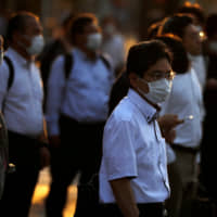 Office workers head home at sunset amid the COVID-19 outbreak in Tokyo. | REUTERS