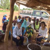 Fuji Oil Holdings Inc. employees pose with local farmers in Burkina Faso in July 2018. Fuji Oil Group is conducting research on sustainable procurement of soybeans, as well as improving the health of area residents through development of soybean meat substitutes. | COURTESY OF  FUJI OIL HOLDINGS INC.
