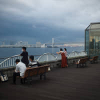 Visitors wearing face masks look at the view from a deck at the Takeshiba Passenger Terminal in Tokyo on Sept. 2. | BLOOMBERG