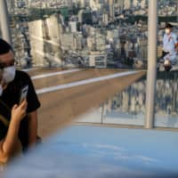 A mask-wearing couple looks at a mobile phone at the Shibuya Sky observation deck in Tokyo on Tuesday. | AFP-JIJI