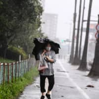 A woman wearing a face mask walks in heavy rain as Typhoon Haishen approaches in the city of Kagoshima on Sunday. | AFP-JIJI