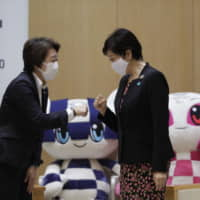 Tokyo Gov. Yuriko Koike (right) meets with Minister for the Tokyo Olympic and Paralympic Games Seiko Hashimoto at the Tokyo Metropolitan Government Building in Tokyo on Sept. 18. | AP