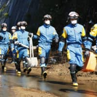 Mask-wearing police officers head to the site of a construction company that was caught in a landslide in Shiiba, Miyazaki Prefecture, on Monday after a storm passed through the Kyushu region. | KYODO
