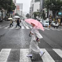A woman crosses a street in Tokyo on Sept. 24. | AFP-JIJI