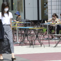 People enjoy lunch outside a restaurant as passers-by wear face masks in Tokyo on Sept. 15. | AP