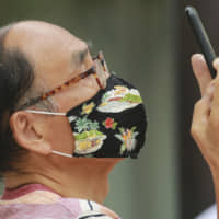 A man wearing a face mask to protect against the spread of the new coronavirus takes pictures in Tokyo on Wednesday. | AP