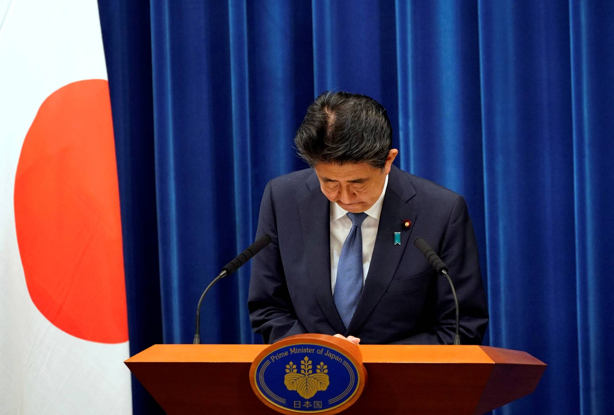 Prime Minister Shinzo Abe bows during a news conference at the Prime Minister's Office in Tokyo on Friday, during which he announced his intention to step down. | POOL / VIA REUTERS