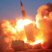 A North Korean missile is fired in this image released on March 22. Outgoing Prime Minister Shinzo Abe will set the policy direction on whether Japan will acquire a strike capability against missile bases in other countries, government sources said Monday. | KCNA / VIA REUTERS