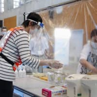 Officials set up an evacuation center with measures against the coronavirus during a disaster drill in Tokushima Prefecture on Tuesday. | KYODO
