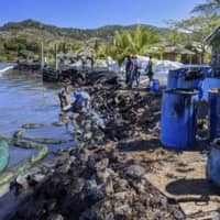 People clean up oil on the coast of Mauritius on Aug. 14. | JAPAN INTERNATIONAL COOPERATION AGENCY / VIA KYODO