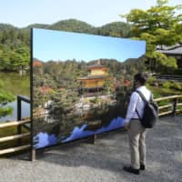 A large photo panel was set up at Kinkakuji temple in Kyoto on Tuesday, as renovation work that started the same day will prevent visitors from viewing the famed golden pavilion. | KYODO