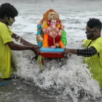 People wearing protective masks due to the COVID-19 pandemic carry an idol of the Hindu god Ganesh, the deity of prosperity, for immersion off the coast of the Arabian sea during the Ganesh Chaturthi festival in Mumbai on Aug. 23. | REUTERS