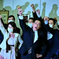 LDP Policy Research Council Chairman Fumio Kishida (center) raises his fist in the air with his faction members after announcing his candidacy for the LDP leadership during a meeting in Tokyo on Tuesday. | AFP